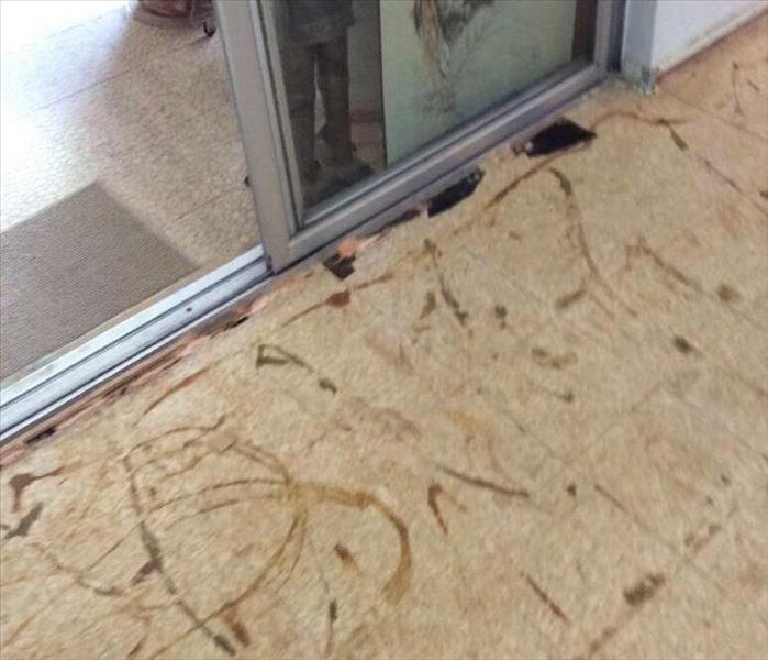 floor of home with flooring removed revealing the plywood and where it meets the sliding glass door.