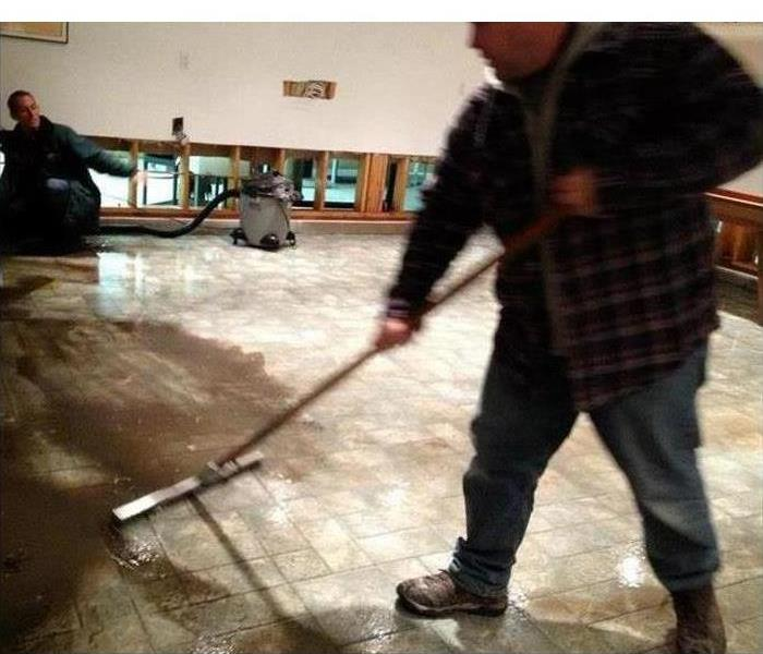Man cleaning floor, water with mud on floor, restoration process in a building